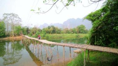 Man passing bamboo bridge by motorbike — Stock Video