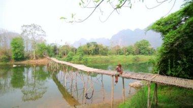 Tourist girl sitting on bamboo bridge — Stock Video