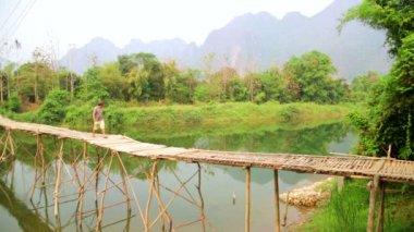 Man crossing river on bamboo bridge — Stock Video