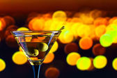 Glass with martini and green olives — Stock Photo