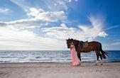 Beautiful girl with horse on seacoast — Stock Photo