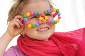 Portrait of cute little girl wearing funny glasses, decorated with colorful sweets, smarties, candies. Four years old child having fun, smiling — Stock Photo
