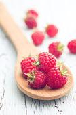 Raspberries on wooden spoon — Stockfoto