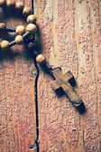 Rosary on old wooden table — Stock Photo