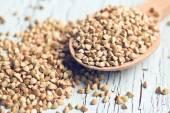 Uncooked buckwheat on wooden spoon — Stock Photo