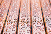 Water drops on wooden garden table — Stock Photo