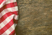 Red tablecloth over old wooden table — Stock Photo
