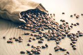 Coffee beans spill out of the sack — Stock Photo