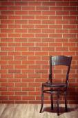 Wooden chair before brick wall — ストック写真