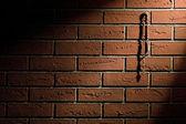 Rosary beads hanging on brick wall — Stockfoto