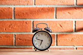 Old clock in front of a brick wall — Stock Photo