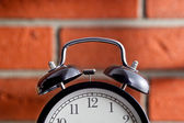Old clock in front of a brick wall — Stockfoto