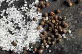 salt crystals and black peppercorns — Stock Photo