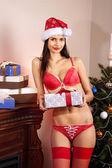 Santa-girl in bikini with present — Stock Photo
