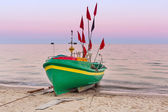 Baltic beach with fishing boat at sunset — Stock Photo