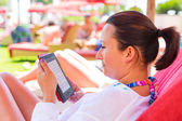 Reading on electronic book on summer holidays — Stok fotoğraf