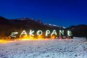 Zakopane sign under Tatra mountains at night — Foto de Stock