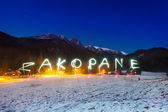Zakopane sign under Tatra mountains at night — Zdjęcie stockowe