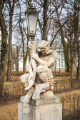 Lantern decorated by sculpture of satyr in Royal Baths Park of Warsaw — Stock Photo