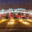 National Stadium in Warsaw illuminated at night by national colors, Poland — Stock Photo #67304299