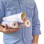 Handyman carrying rolls of wallpaper — Stock Photo #70447077