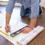 Handyman measuring wallpaper to cut — Stock Photo #70447151