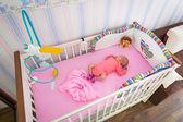 Dziecko dziewczynka kołyski w pokoju dziecka — Zdjęcie stockowe
