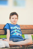 Sad boy sitting on a bench — Stock Photo
