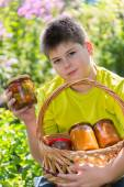 Boy and home canned vegetables in nature — Stock Photo