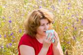 Fat woman with allergic rhinitis in  meadow — Stock Photo