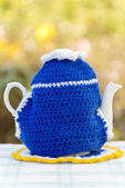 Knitted doily on the teapot in  natural background. — Stock Photo