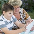 Granny with grandson watching tablet in nature — Stock Photo #56648893