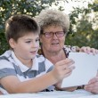 Granny with grandson watching tablet in nature — Stock Photo #56648913