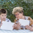 Granny with grandson watching tablet in nature — Stock Photo #56648995