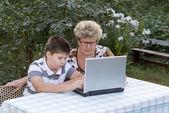 Farmor med en sonson bakom den laptop utomhus — Stockfoto