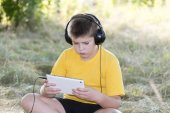 Boy in headphones looking tablet computer on the nature — Stock Photo