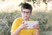 The boy in glasses looks tablet computer at nature — Stock Photo