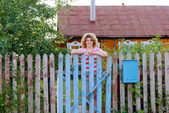 Middle-aged woman stands at the gates country house — Stock Photo