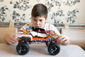 Boy plays collects from the constructor of  car — Stock Photo