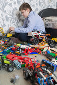 Teenage boy playing with toy cars in  room — Stock Photo