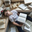 Tired boy sleeping surrounded by books in  room — Stock Photo #60261123