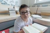Boy with glasses reading a book in  room — Foto Stock
