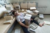 Tired boy sleeping surrounded by books in  room — Foto Stock