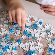 Teenager boy collects puzzles at  table — Stock Photo #60669683