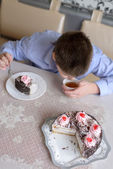 Boy eating cake at  table — Stock Photo