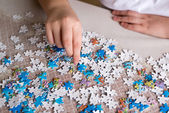 Teenager boy collects puzzles at  table — Stock Photo