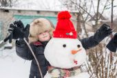 The boy in a fur hat around snowman — Стоковое фото