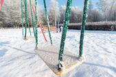 Snow covered swing and slide at playground in winter — Foto de Stock
