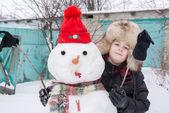 De jongen in een bont hoed rond sneeuwpop — Stockfoto