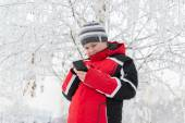 Teenager boy writes sms in winter park — Stock Photo